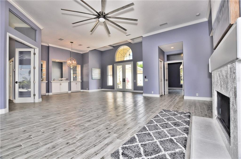 the formal living room with a fireplace  opens into the remodeled kitchen and pool area overlooking the Myakka River. - Single Family Home for sale at 3121 Rivershore Ln, Port Charlotte, FL 33953 - MLS Number is D5917816