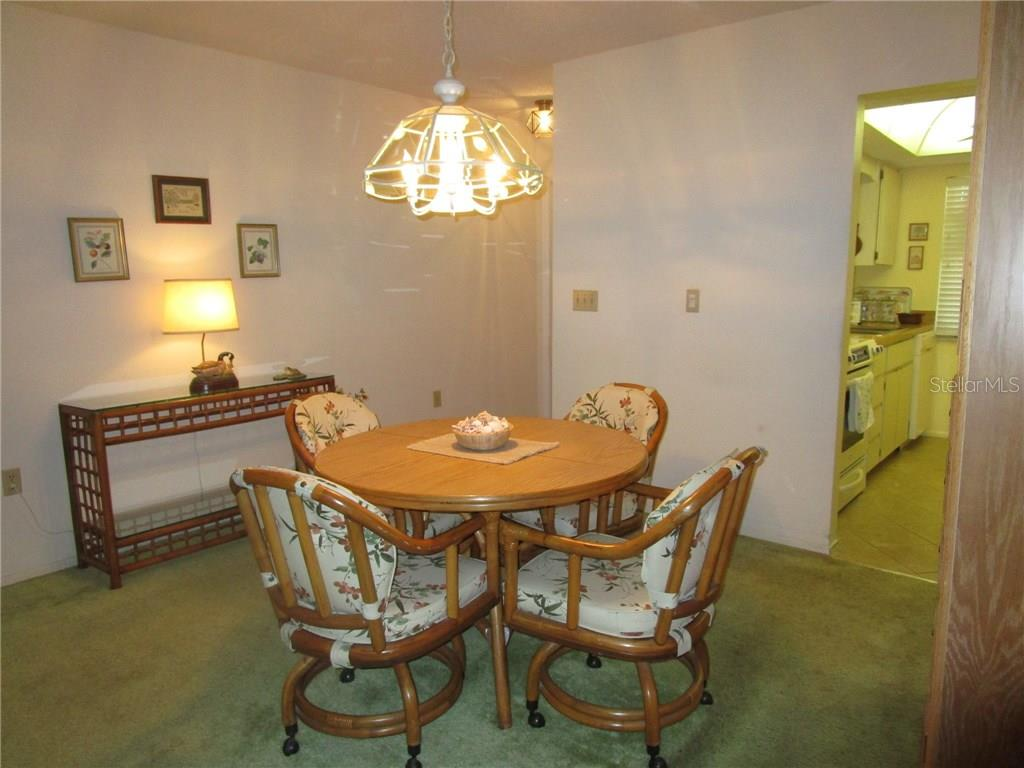 Dining room is just outside the galley kitchen and has chandelier & carpeted flooring. - Condo for sale at 6796 Gasparilla Pines Blvd #14, Englewood, FL 34224 - MLS Number is D5919892