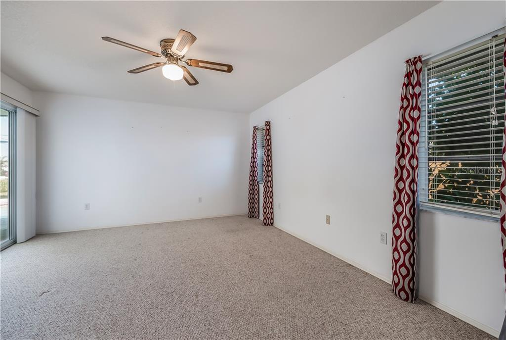 Master bedroom with sliding doors out to the lanai and pool area. - Single Family Home for sale at 11010 Deerwood Ave, Englewood, FL 34224 - MLS Number is D5921766