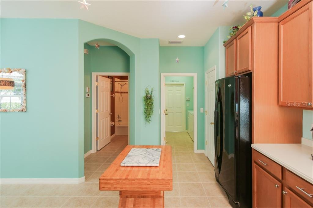 As we turn around, this is a look back toward the laundry room on the right and the guest bathroom to the left. - Villa for sale at 29704 Niagara Ct, Englewood, FL 34223 - MLS Number is D6102386
