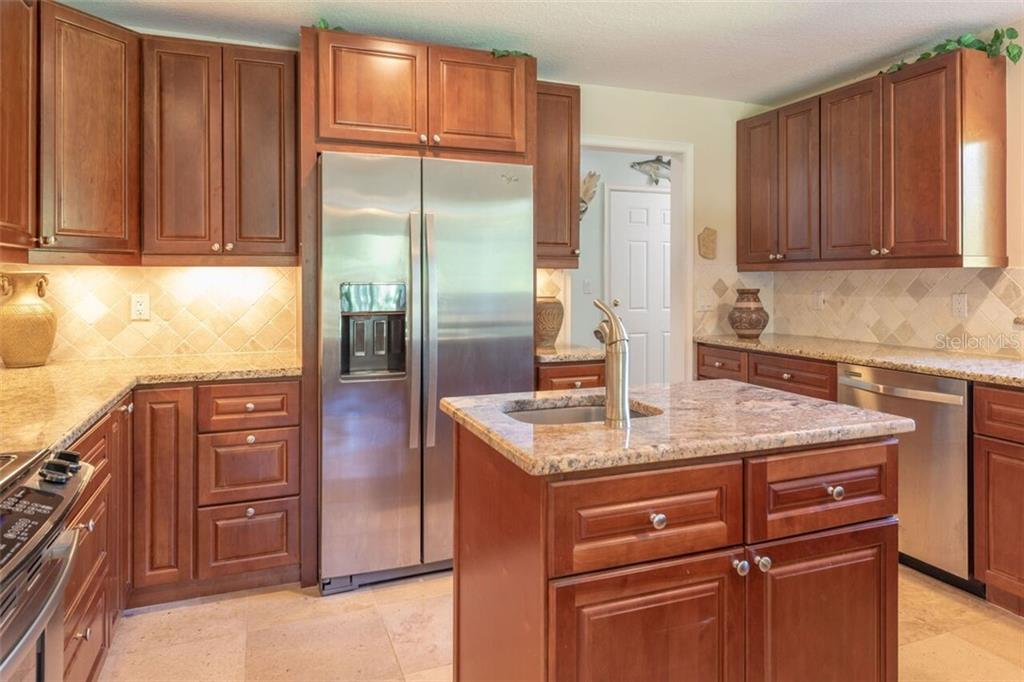 The tumbled marble back splash is high lighted by the lighting.  Fewer kitchens have ever been built with more storage. - Single Family Home for sale at 7339 Hawkins Rd, Sarasota, FL 34241 - MLS Number is D6102762
