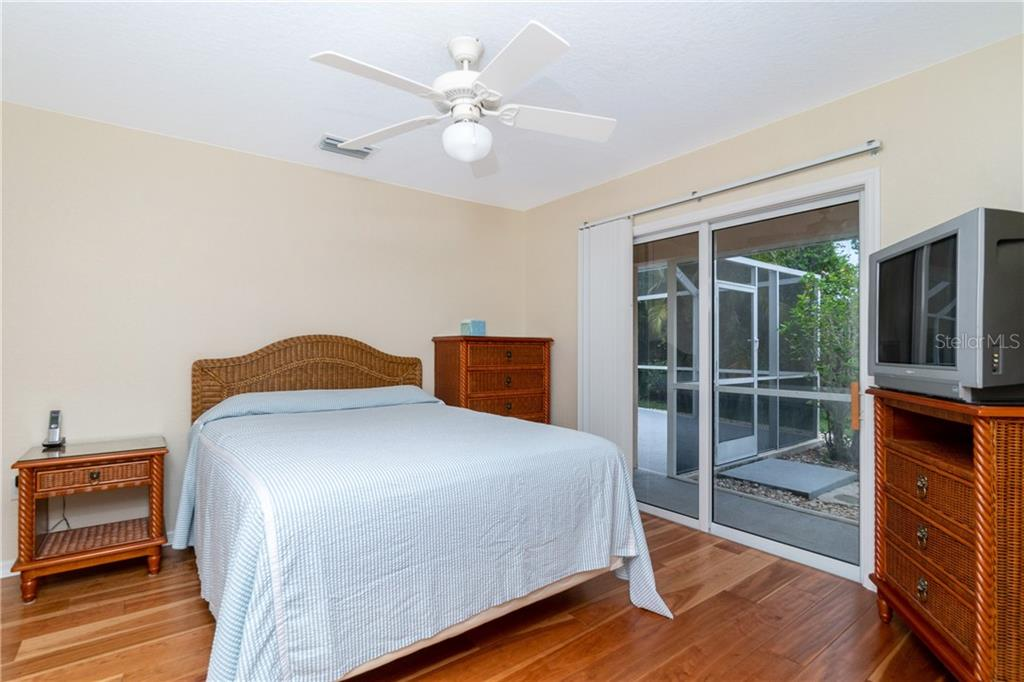 Guest bedroom 3 has sliding glass doors to Lanai. - Single Family Home for sale at 30 Medalist Way, Rotonda West, FL 33947 - MLS Number is D6106239