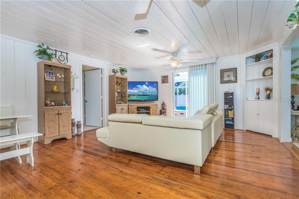 Living area with original hardwood floors, with sliding doors out to the private, screened hot tub area - Single Family Home for sale at 190 W Wentworth St, Englewood, FL 34223 - MLS Number is D6106918