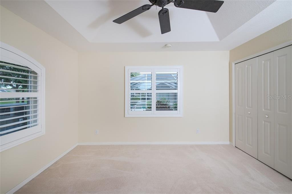 Bedroom #3 is complimented by plantation shutters & tray ceilings - Single Family Home for sale at 254 Rotonda Blvd E, Rotonda West, FL 33947 - MLS Number is D6107401