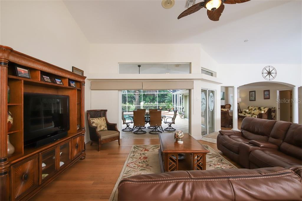 Living Room overlooks pool & lanai - Single Family Home for sale at 254 Rotonda Blvd E, Rotonda West, FL 33947 - MLS Number is D6107401