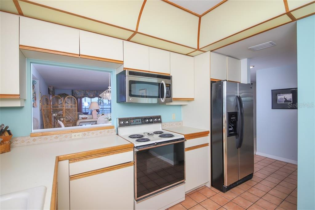 Kitchen looks out into Dining Room-Living Room - Condo for sale at 11000 Placida Rd #2501, Placida, FL 33946 - MLS Number is D6112229