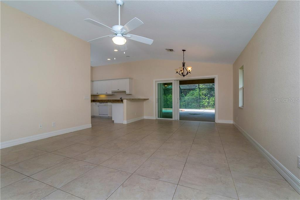 ANOTHER LOOK AT THE GREAT ROOM. THE BREAKFAST BAR IS TO THE LEFT OF THE SLIDING DOORS. - Single Family Home for sale at 112 Boxwood Ln, Rotonda West, FL 33947 - MLS Number is D6114179
