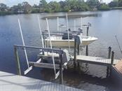 The larger lift is a #10,000 lift, the smaller one is a #3,500 lift.  Just out of view to the left is a jet ski lift.  The deck is made from top-of-the-line composite material. - Single Family Home for sale at 1439 Deer Creek Dr, Englewood, FL 34223 - MLS Number is D5921060