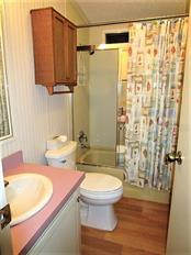 Guest bath has laminate flooring and combination tub/shower. - Manufactured Home for sale at 1800 Englewood Rd #95, Englewood, FL 34223 - MLS Number is D6103776