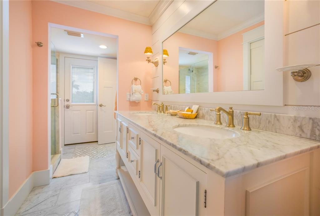 The ensuite bathroom for the ground floor master bedroom has a Carrera marble double vanity, private water closet, and walk-in shower - Single Family Home for sale at 511 Loquat Dr, Anna Maria, FL 34216 - MLS Number is T3196169