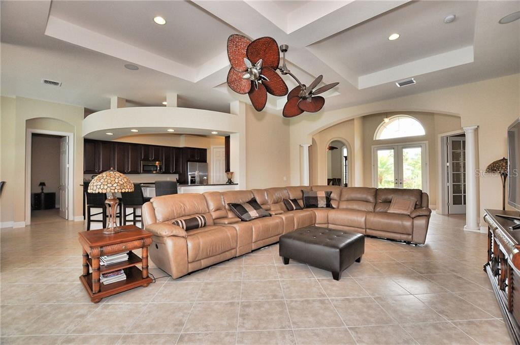 Spectacular view of the open floor plan of your spacious great room, featuring coffered ceiling and decorative columns, with a soothing neutral tone of diagonal ceramic flooring and paint selection. - Single Family Home for sale at 2839 Mill Creek Rd, Port Charlotte, FL 33953 - MLS Number is C7238545