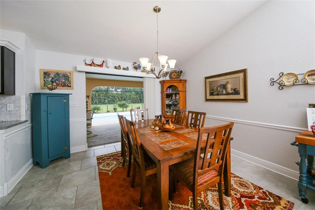Dining room with chair rail and lovely view to the outdoors - Single Family Home for sale at 26178 Rampart Blvd, Punta Gorda, FL 33983 - MLS Number is C7240559