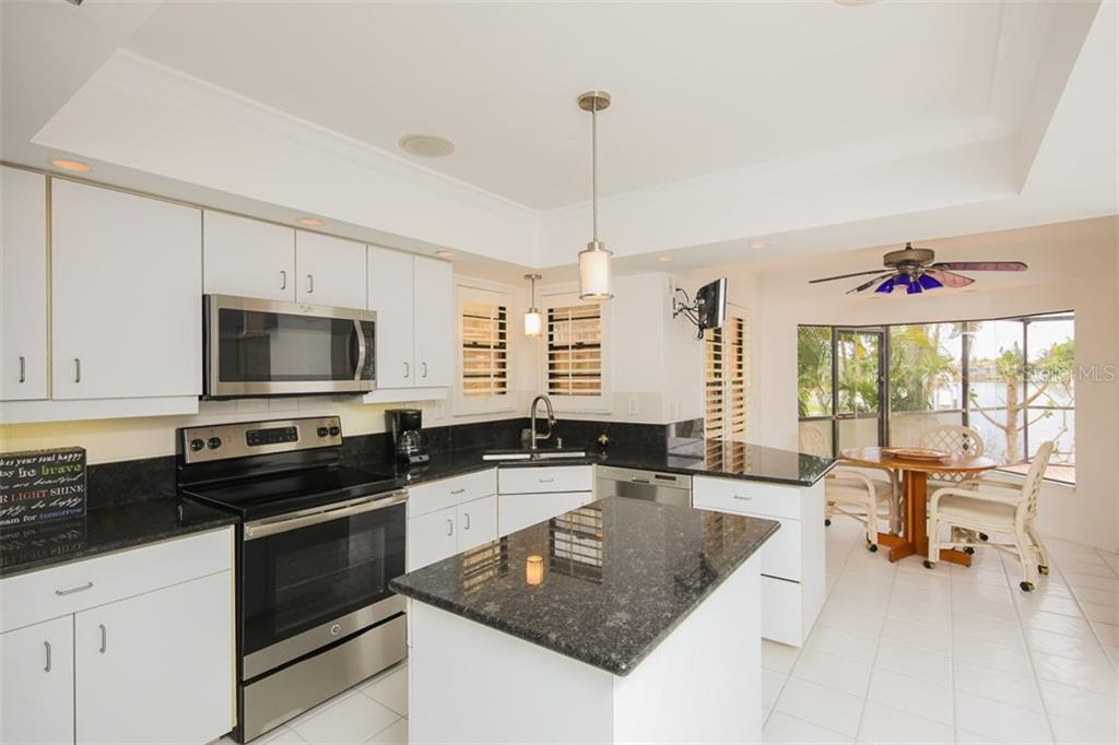 Granite counters and stainless steel appliances enhance this kitchen that opens to the dining and great rooms - Single Family Home for sale at 1620 Appian Dr, Punta Gorda, FL 33950 - MLS Number is C7242315