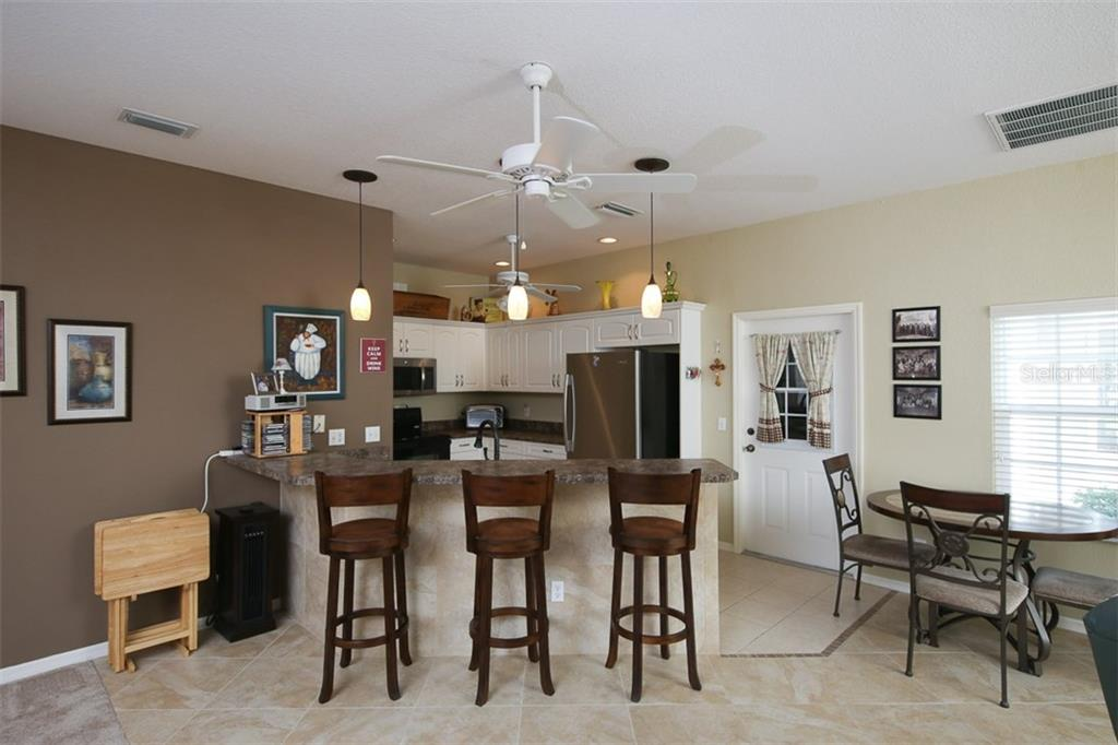 Kitchen opens into the great room with dining nook area to the right - Villa for sale at 1268 Green Oak Trl, Port Charlotte, FL 33948 - MLS Number is C7243755