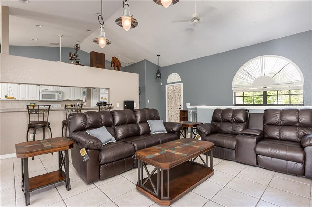 Living/Great Room extending to screened lanai, pool, fenced yard and mature landscaping - Single Family Home for sale at 515 Royal Poinciana Cir, Punta Gorda, FL 33955 - MLS Number is C7244338