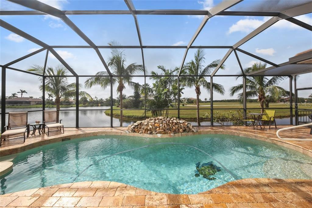 Turkish stone tile surrounds the heated free form pool that boasts a rock waterfall and submerged cocktail table. You will certainly enjoy watching the wildlife that is attracted to the lake in your backyard. - Single Family Home for sale at 17208 Barcrest Ln, Punta Gorda, FL 33955 - MLS Number is C7245458