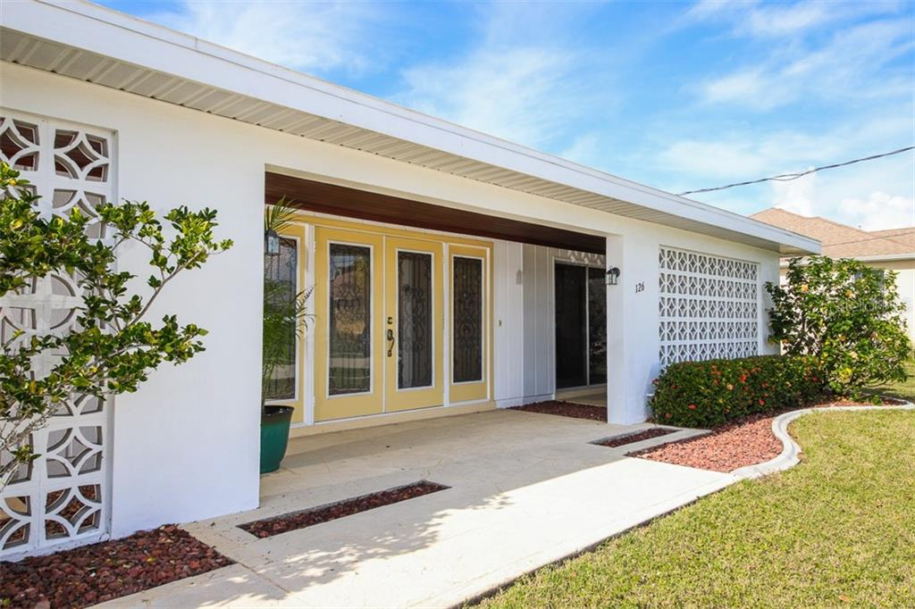 Wood ceilinged entry porch with impact front doors diffuses light filtered from the east facing front elevation. - Single Family Home for sale at 126 Bangsberg Rd Se, Port Charlotte, FL 33952 - MLS Number is C7409866