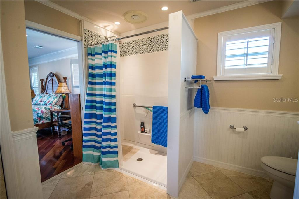 New roll-in tiled shower and Wainscoating give the ensuite bath a fresh, light feel. - Single Family Home for sale at 1440 Appian Dr, Punta Gorda, FL 33950 - MLS Number is C7425399