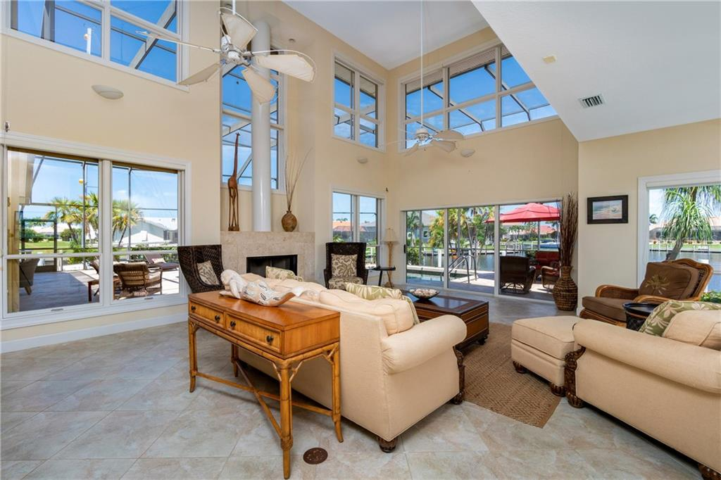 FAMILY ROOM WITH WOODBURNING FIREPLACE, TWO STORY CEILINGS, TONS OF NATURAL LIGHT AND SLIDERS TO LANAI - Single Family Home for sale at 3537 Caya Largo Ct, Punta Gorda, FL 33950 - MLS Number is C7431664