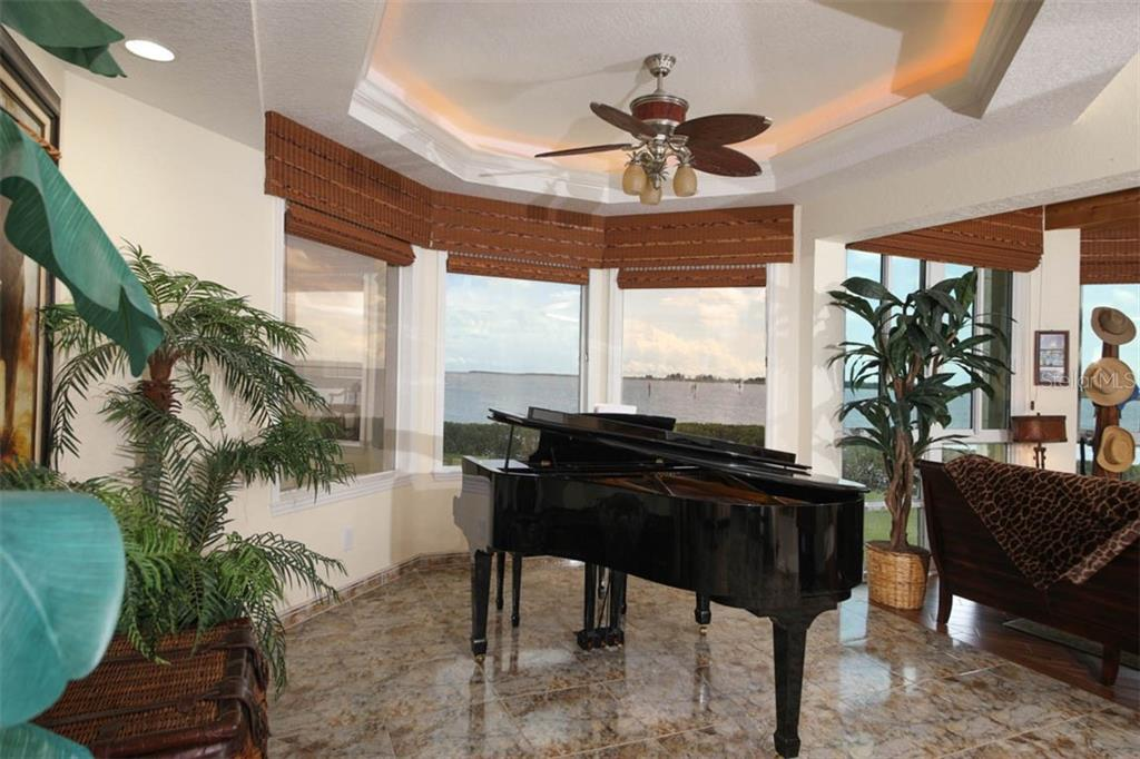The dining room shown in the previous photo was used to display this baby grand piano. High ceilings and custom lighted, tray ceilings appear throughout this home. - Condo for sale at 4410 Warren Ave #511, Port Charlotte, FL 33953 - MLS Number is C7432222