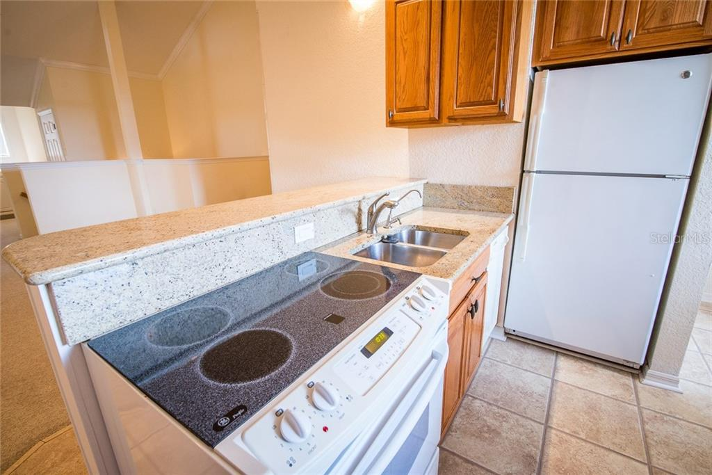 Third-floor kitchen includes full-size appliances, a breakfast bar, stackable washer and dryer and eat-in space. - Condo for sale at 4410 Warren Ave #511, Port Charlotte, FL 33953 - MLS Number is C7432222