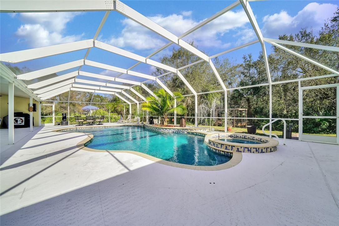Heated pool, spa, sun shelf, pebble tech finish, water features - Single Family Home for sale at 10230 Sw County Road 769, Arcadia, FL 34269 - MLS Number is C7437596