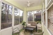The far end of the lanai features a solar shade to filter the sunshine.  What a cozy sitting area that compliments the al fresco dining area! - Villa for sale at 3181 Matecumbe Key Rd #6, Punta Gorda, FL 33955 - MLS Number is C7409111