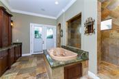 Walk-in closets, and en-suite baths fit for royalty featuring marble flooring, dual vanities, jetted tubs, and Roman showers with dual shower heads - Single Family Home for sale at 7440 Riverside Dr, Punta Gorda, FL 33982 - MLS Number is C7436263