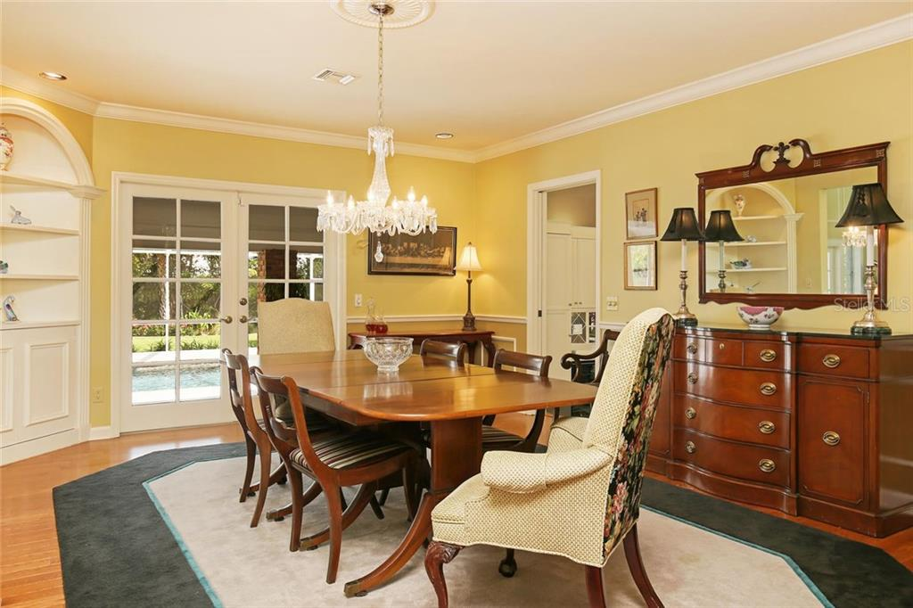 Formal dining room with chandelier, hardwood floors, crown molding, double doors to lanai, built-in shelving and cabinetry and easy access to kitchen. - Single Family Home for sale at 3765 Beneva Oaks Blvd, Sarasota, FL 34238 - MLS Number is A4185879