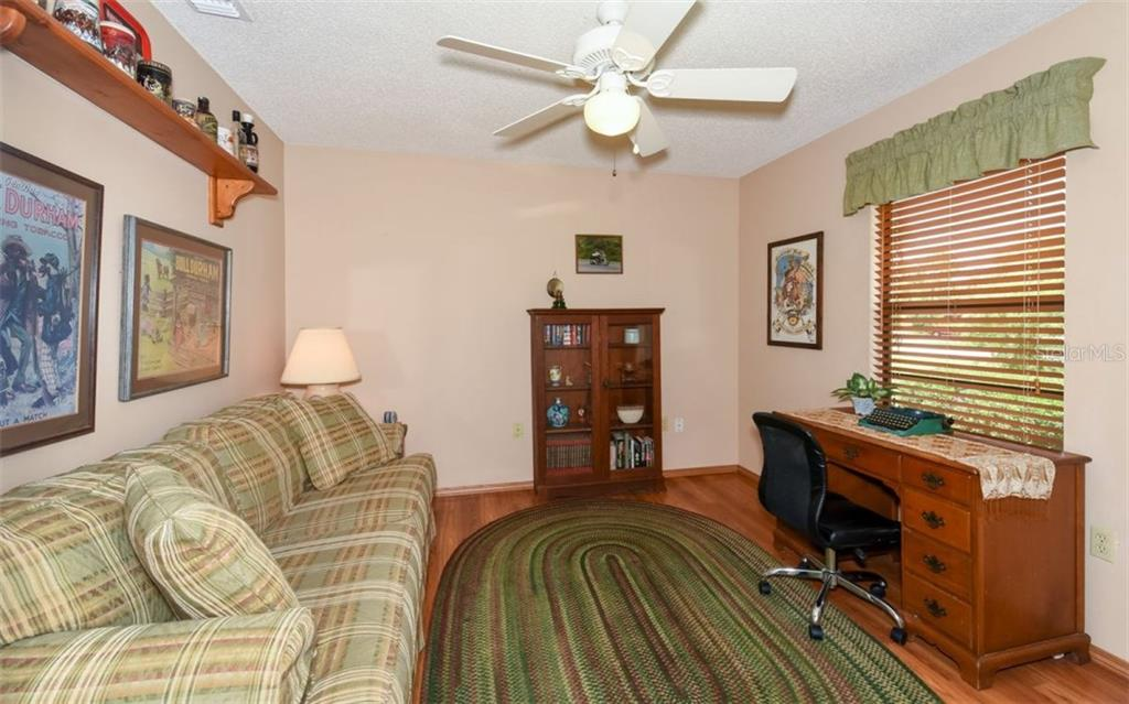 Bedroom #2 with laminate flooring, currently being used as a Den - Single Family Home for sale at 9534 59th Ave E, Bradenton, FL 34202 - MLS Number is A4188099