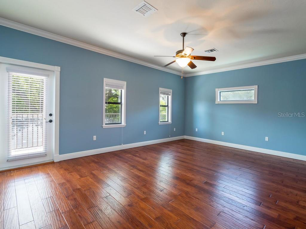 Crown molding and wood floors in this Master bedroom along with a private glass paneled door leading to open balcony overlooking backyard area. - Single Family Home for sale at 1884 Grove St, Sarasota, FL 34239 - MLS Number is A4189365