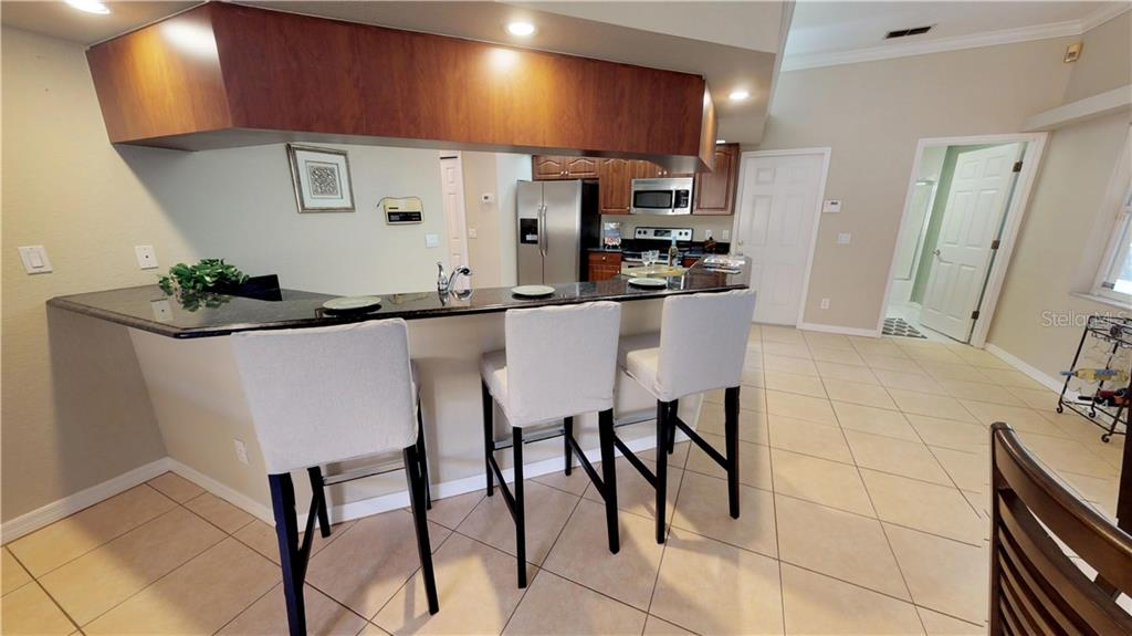 The large, wrap around bar could easily handle many more barstools for a large family or friends! - Single Family Home for sale at 9122 16th Avenue Cir Nw, Bradenton, FL 34209 - MLS Number is A4189396