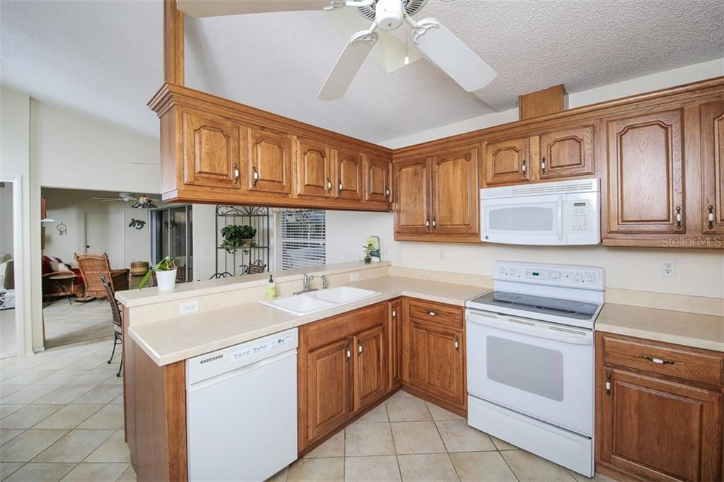 kitchen overlooks eat in sitting area and view of pool and lake. - Single Family Home for sale at 3610 Garden Lakes Clenet, Bradenton, FL 34203 - MLS Number is A4193334