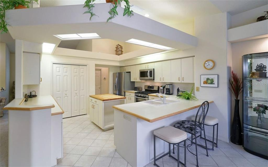 The Kitchen features a Breakfast Bar with new appliances - Refrigerator, Range with Double Oven, Microwave and Dishwasher. - Single Family Home for sale at 3408 Little Country Rd, Parrish, FL 34219 - MLS Number is A4193677