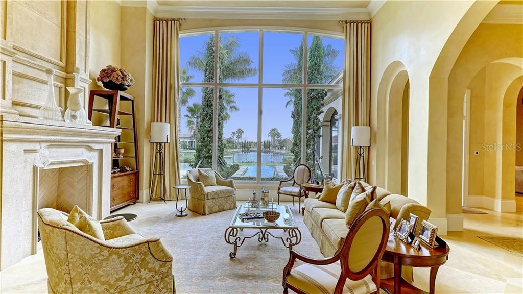 Living room with views through disappearing edge fountain and pool across lake toward distant ballustered bridge - Single Family Home for sale at 16014 Foremast Pl, Lakewood Ranch, FL 34202 - MLS Number is A4194540
