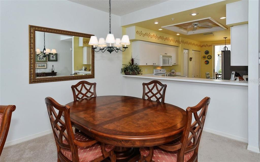 Dining area with close up picture of the large pass-thru to kitchen and breakfast bar. - Condo for sale at 9570 High Gate Dr #1712, Sarasota, FL 34238 - MLS Number is A4196327