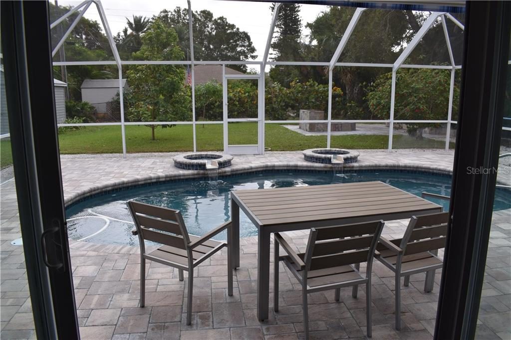 Your view through 12' impact sliders from the living room to the large backyard, fire pit/BBQ and patio. - Single Family Home for sale at 1133 Riviera St, Venice, FL 34285 - MLS Number is A4197682