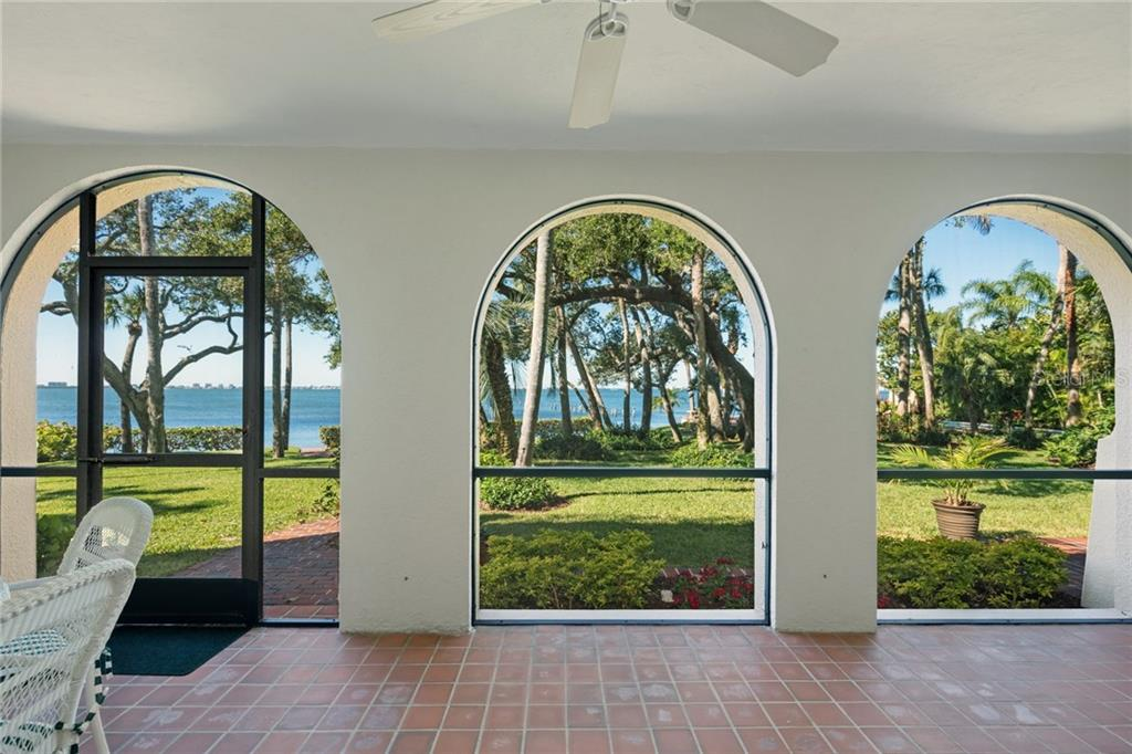 Screened lanai with original tile and arches framing the view to the bay front and private back yard - Single Family Home for sale at 3221 Bay Shore Rd, Sarasota, FL 34234 - MLS Number is A4200323
