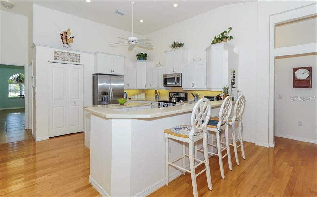 Kitchen with Hardwood Floors Large Breakfast Bar Stainless Appliances with Bonus Room to the left - Single Family Home for sale at 460 Otter Creek Dr, Venice, FL 34292 - MLS Number is A4205372