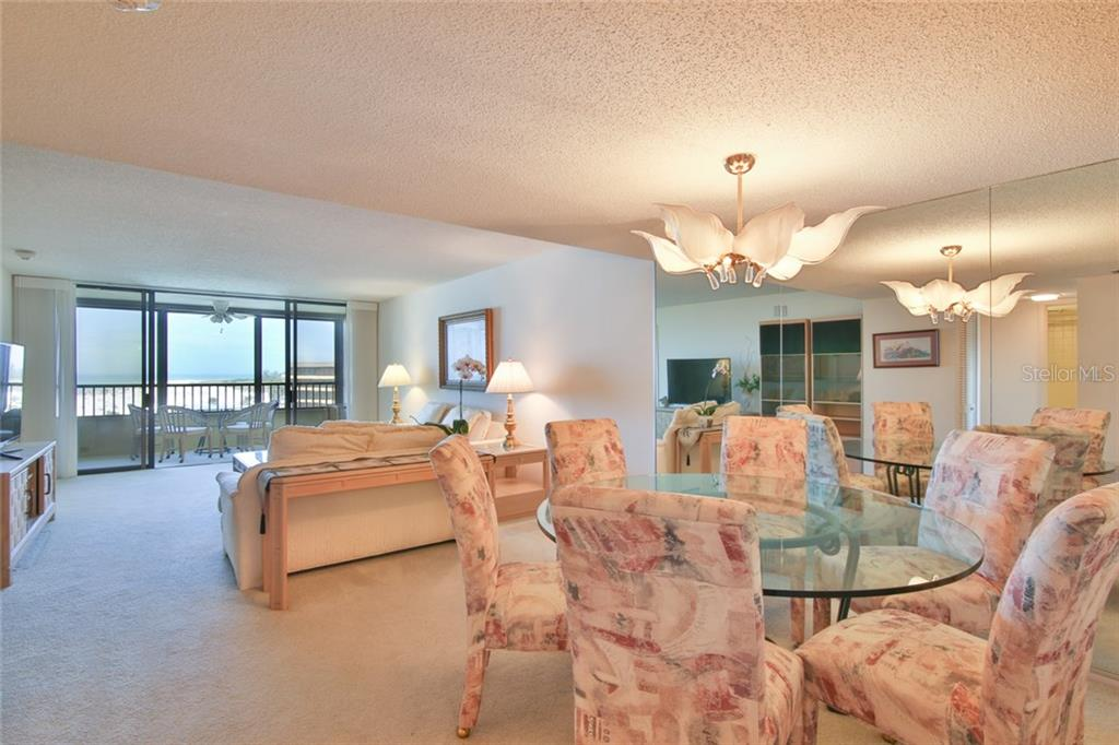 Open plan of dining room and living room straight through for full views - Condo for sale at 5790 Midnight Pass Rd #704, Sarasota, FL 34242 - MLS Number is A4208095