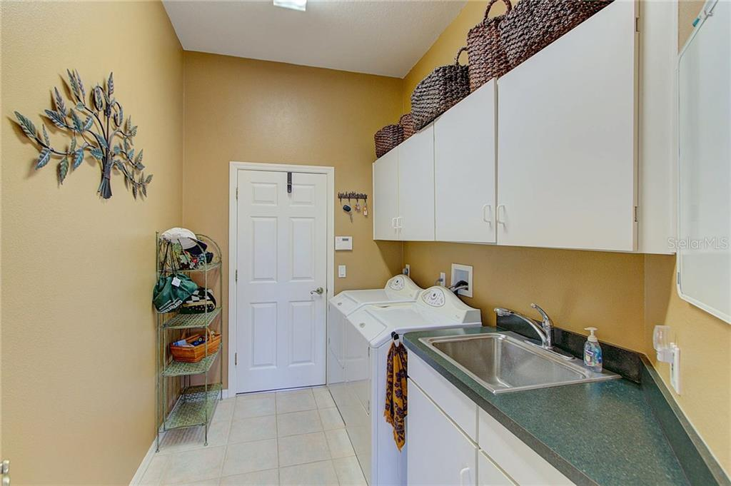 Inside laundry/utility with sink and cabinets, leads to spotless garage with epoxy flooring. - Single Family Home for sale at 4810 76th Ct E, Bradenton, FL 34203 - MLS Number is A4208531