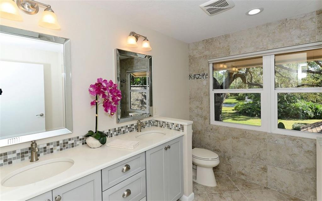 Full guest ensuite bathroom with dual sinks. - Single Family Home for sale at 5122 Willow Leaf Dr, Sarasota, FL 34241 - MLS Number is A4209555