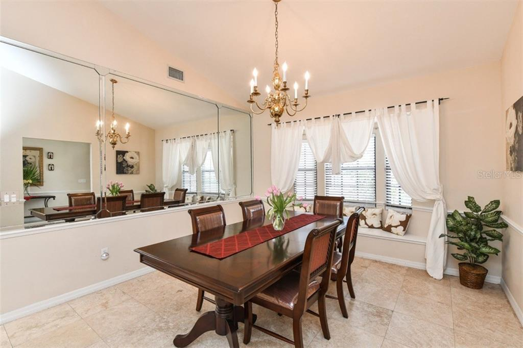 Formal Dining Room with Bay Window and a mirrored wall. - Single Family Home for sale at 7536 Weeping Willow Dr, Sarasota, FL 34241 - MLS Number is A4210209