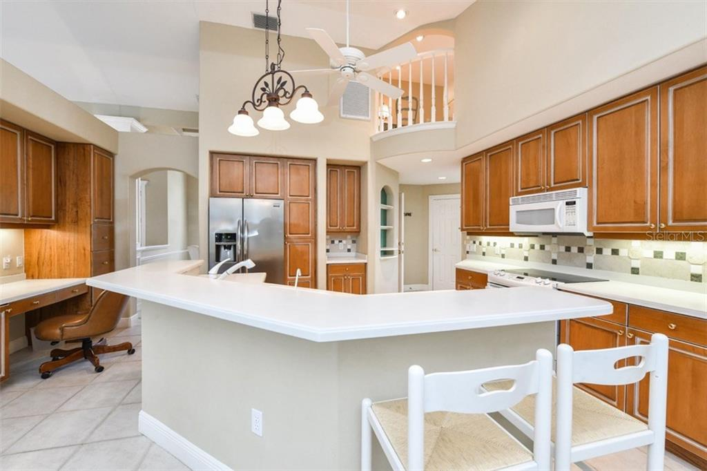 The view from the Great Room to the Kitchen, Breakfast Area, and Loft, with soaring cathedral ceilings and abundant recessed lighting. - Single Family Home for sale at 5585 Siesta Estates Ct, Sarasota, FL 34242 - MLS Number is A4211109