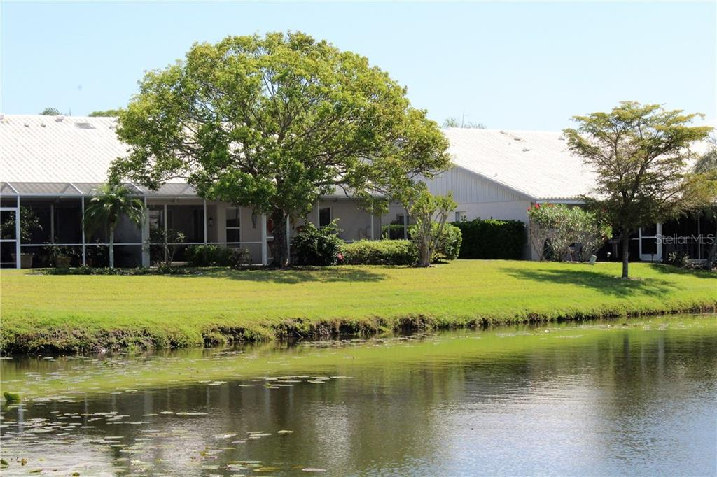Looking from across the pond, to the back of the unit beyond the towering oak. - Villa for sale at 5438 Kelly Dr #12, Sarasota, FL 34233 - MLS Number is A4400319