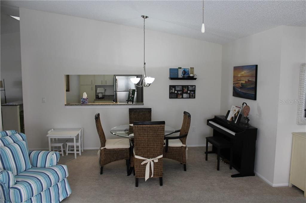 View from living room to dining room and kitchen pass-through opening.  Note towering ceilings. - Villa for sale at 5438 Kelly Dr #12, Sarasota, FL 34233 - MLS Number is A4400319