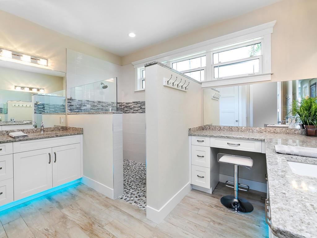 Kitchen with white wood cabinets, light tones of solid surface counters, tiled backsplash, and sliding doors to enclosed patio and to open air pool and spa - Single Family Home for sale at 7643 Cove Ter, Sarasota, FL 34231 - MLS Number is A4403215