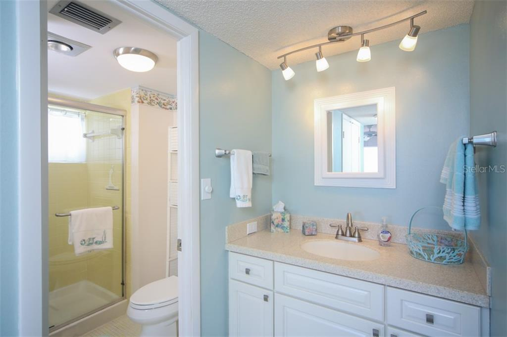 Master bath has been updated with taller vanity, new lighting, elevated toilet and glass shower door. - Condo for sale at 5200 Gulf Dr #101, Holmes Beach, FL 34217 - MLS Number is A4404016