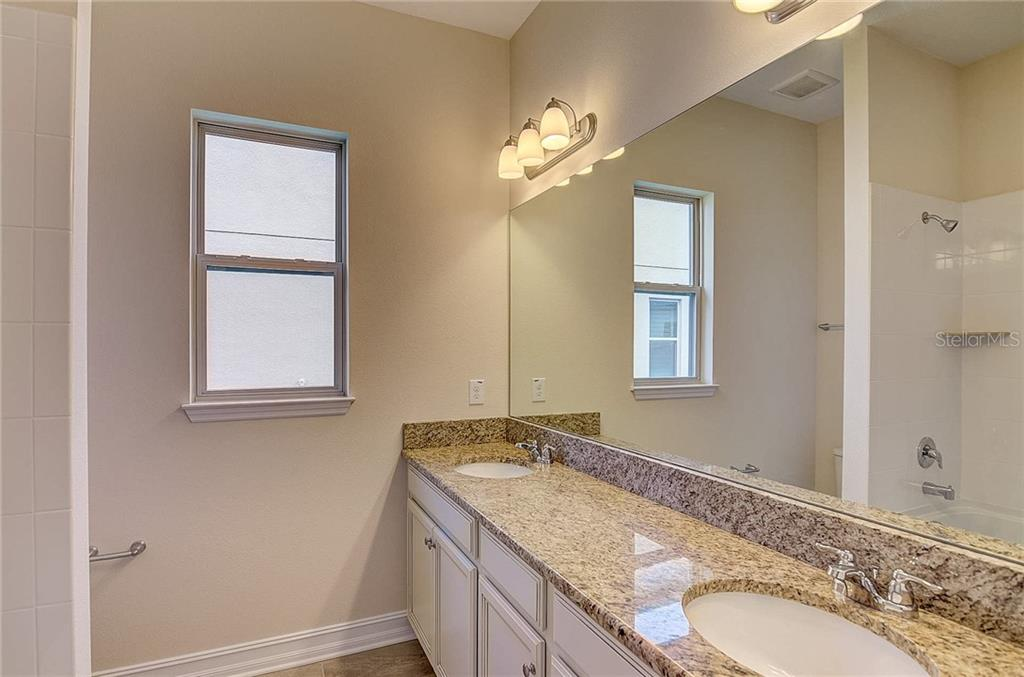 The guest bathroom has double sinks, plenty of counter space, and a shower/tub combo. - Single Family Home for sale at 13019 Utopia Loop, Bradenton, FL 34211 - MLS Number is A4404703