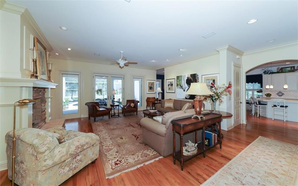 Spacious living room with a large wood-burning fireplace and a great view of the covered back porch and pool lanai! - Single Family Home for sale at 7866 Saddle Creek Trl, Sarasota, FL 34241 - MLS Number is A4407172